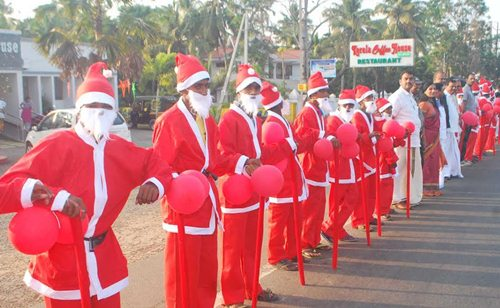 People dressed as Santa Claus participate in the human chain